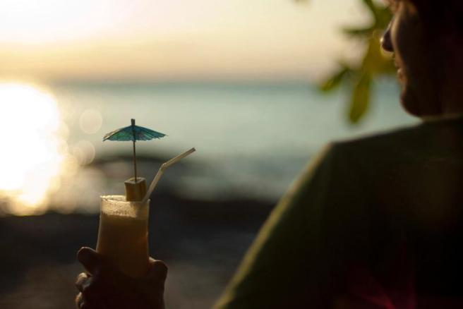 man relaxing with drink watching sunset at beach
